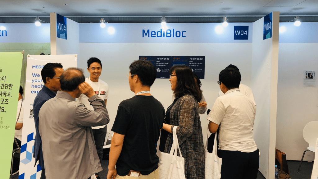 업비트 개발자 컨퍼런스 UDC의 메디블록 메디패스 체험 부스에 관람객들이 방문하여 고우균 대표와 대화를 나누고 있습니다.